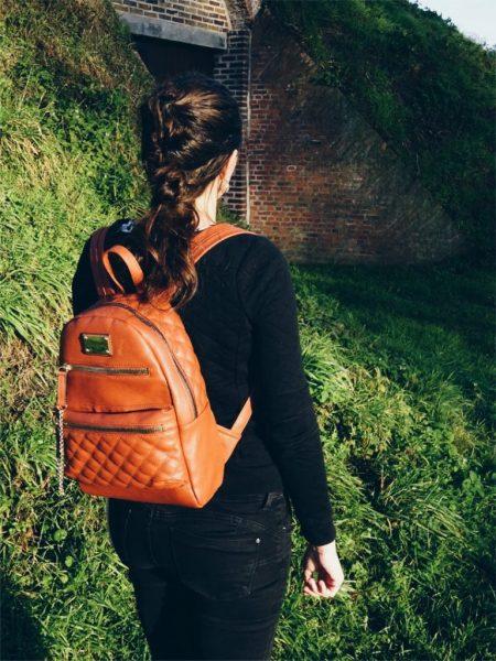 26b55133cc9 De tas is volledig uit leer gemaakt, heeft verstelbare schouderbanden, een  handvat bovenaan, en heeft mooie goudkleurige details. De ritsen zijn  goudkleurig ...